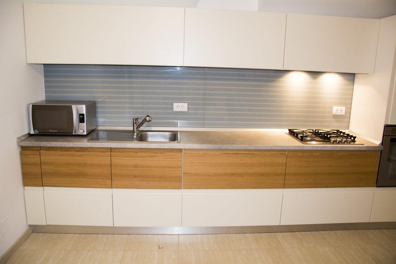 mobila-bucatarie-moderna-realizata-cu-fronturi-din-mdf-vopsit-mat-ral-9003-alb-cu-lemn-masiv-stejar-cu-frezare-maner
