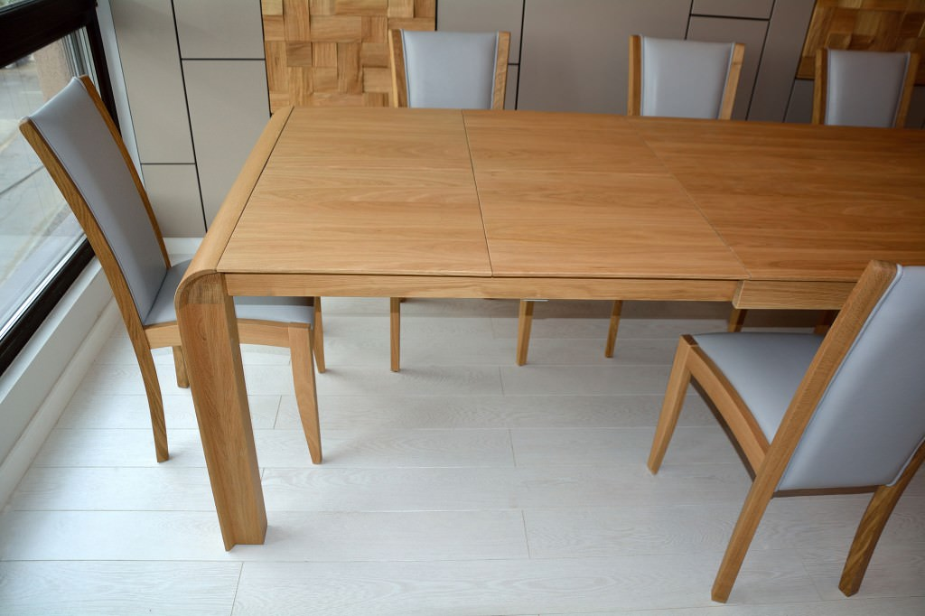 Detaliu masa mobila realizata din lemn masiv natur cu curbura la colturi si 8 scaune din lemn masiv tapitate in piele gri naturala 1024x682 1