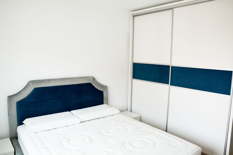 Dormitor matrimonial la comanda cu pat integral tapitat cu stofa Prestige catifea gri si smarald noptiere pal alb fibros dulap pal alb cu usi profil rama aluminiu