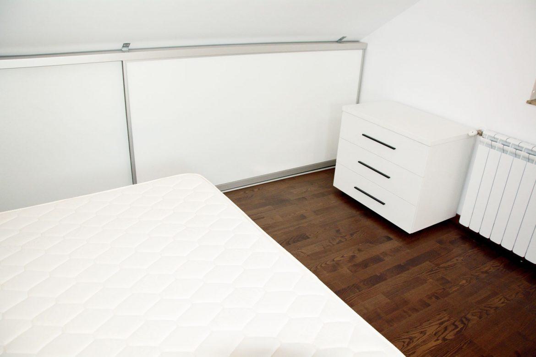 Mobilier dormitor la mansarda realizat la comanda din pal alb fibra pat tapitat piele ecologica alba si dressing mansarda cu tavan inchis cu profil aluminiu si cant ABS de 2 mm