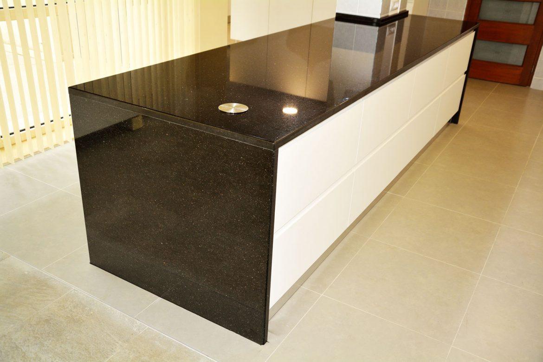 Bucatarie cu insula la comanda cu blat de 30 mm granit negru Galaxy usi MDF vopsit alb mat RAL 9003 cu frezare manere sertare Antaro Blum