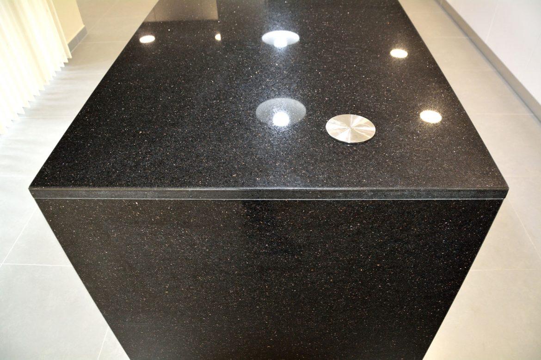 Detaliu blat de 30 mm din granit negru model Galaxy montat pe insula bucatarie la comanda priza rotunda pe blat