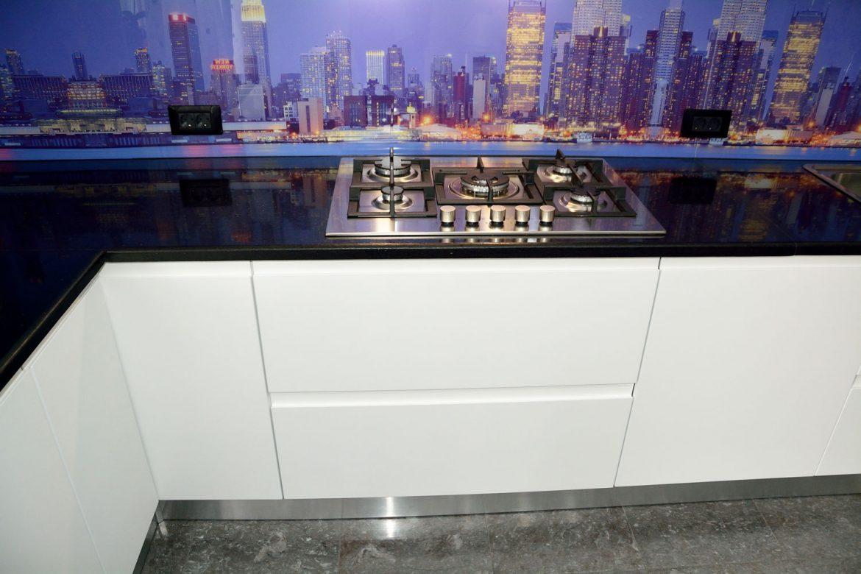 Detaliu bucatarie moderna la comanda Yulmob cu blat granit negru plita inox pe gaz usi MDF vopsit alb mat RAL 9003 cu frezare manere plinta picioare din PVC