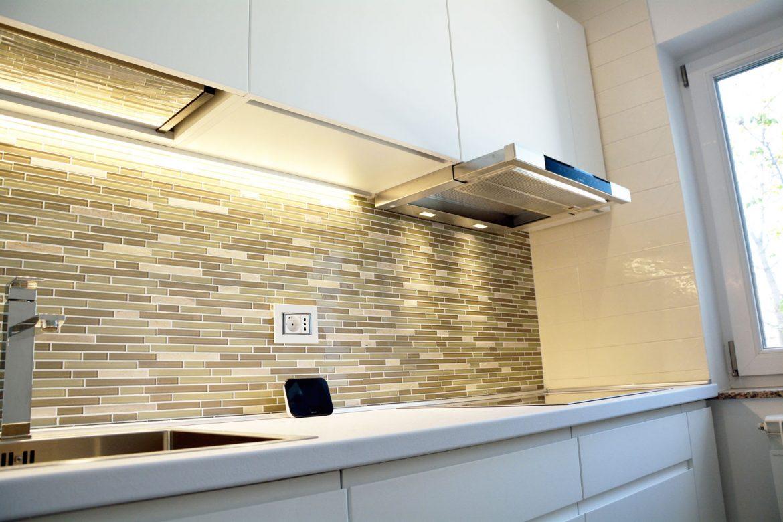 Detaliu bucatarie moderna la comanda cu placare faianta din sticla leduri hota incastrabila Bosch blat termorezistent Egger alb Premium cu cant drept