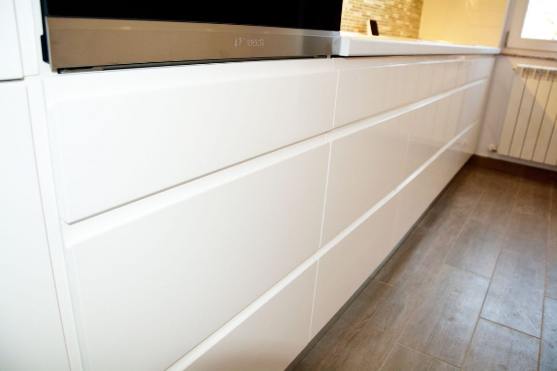 Detaliu front bucatarie la comanda din MDF vopsit RAL 9003 alb lucios cu frezare manere plinta picioare din PVC blat termorezistent alb premium Egger electrocasnice incorporabile Bosch